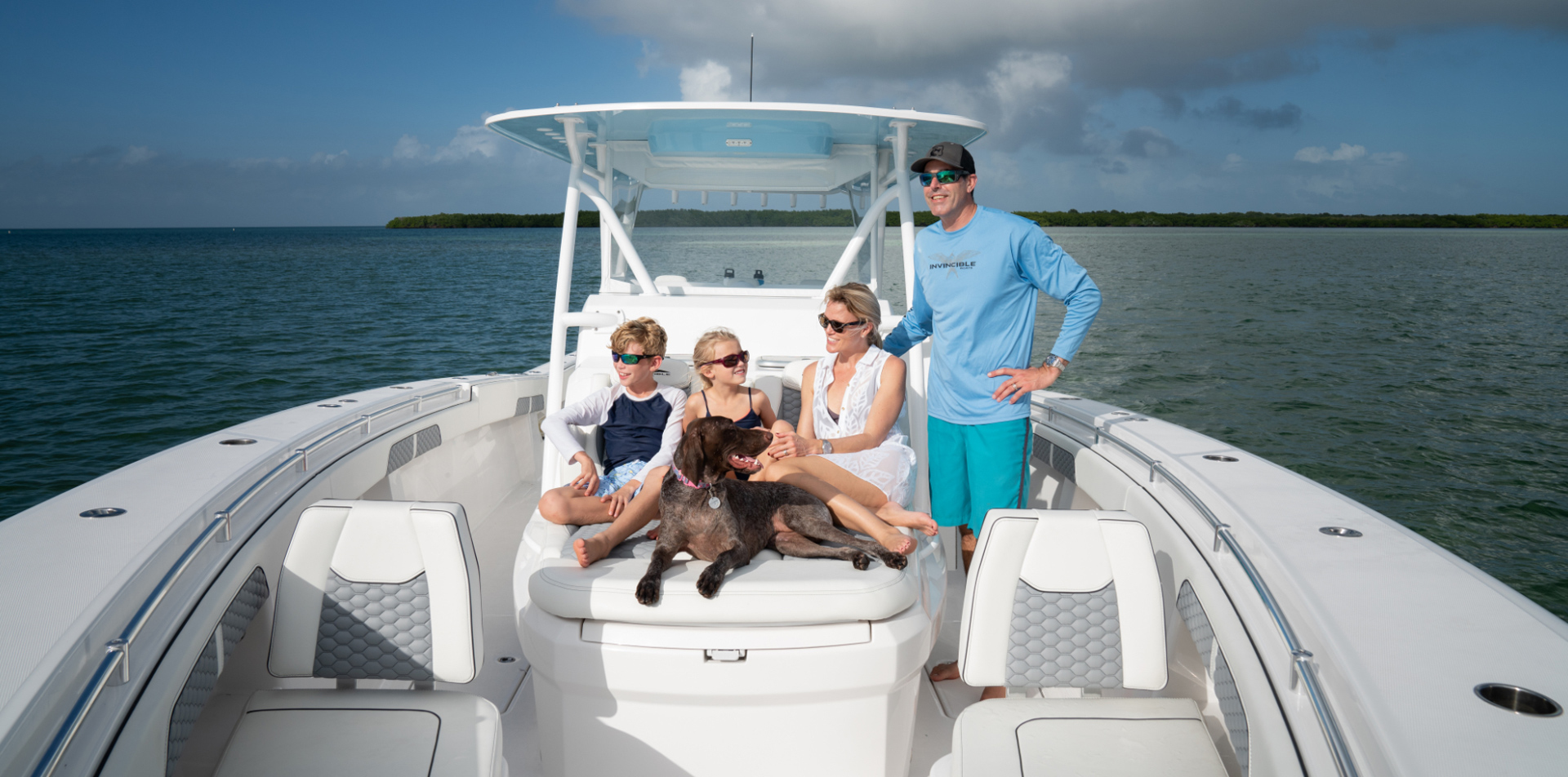 Family and dog enjoying Invincible's custom cushioned seating on the 42 foot Open Fisherman with cabin.