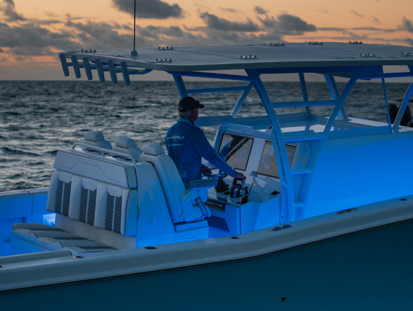 Man navigating the 42 ft. center console boat with cabin. Sunset background and under gunnel lighting.