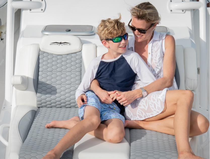 Mother and son enjoying the custom cushioned lounge seating on Invincible's center console boat with cabin.